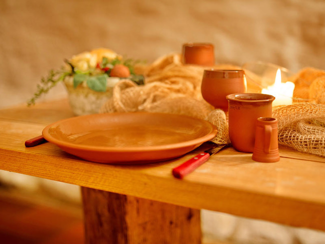 Weinkeller mit gedecktem Esstisch bei Kerzenschein