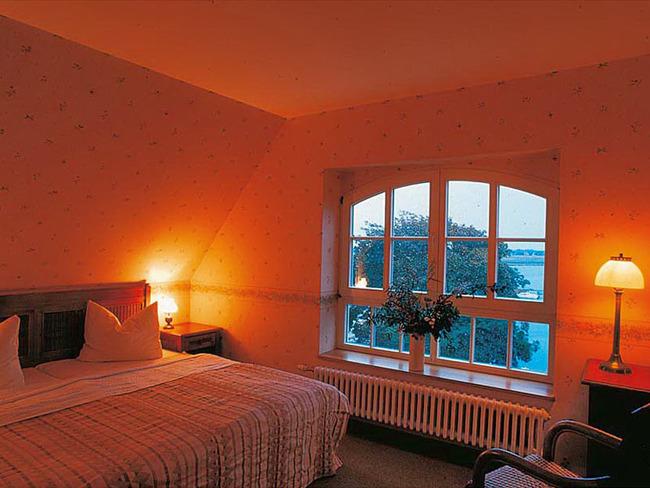 Doppelzimmer im Obergeschoss mit Bett, großem Fenster und Boddenblick