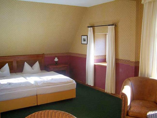 hell und stilvoll eingerichtetes Doppelzimmer mit Sitzecke, Bett und Nachtschrank