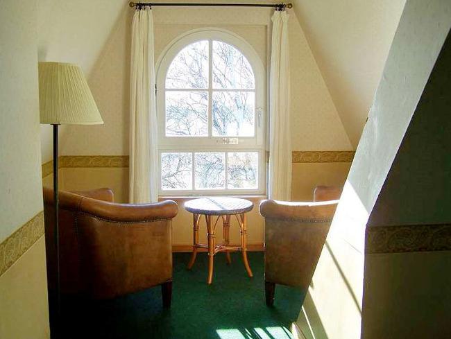 gemütliche Leseecke mit 2 Sesseln, Tisch und Stehlampe im Doppelzimmer