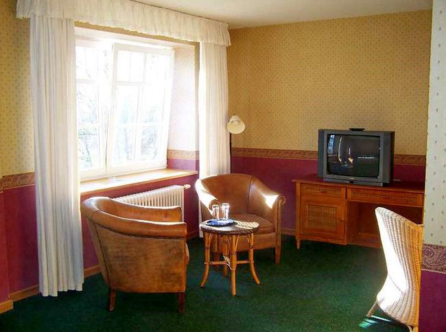 Doppelzimmer mit Sesseln, Tisch, Schreibtisch und Fernseher im rustikalen Stil