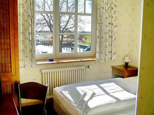 Einzelzimmer mit Bett, Schreibtisch, Schrank und Boddenblick