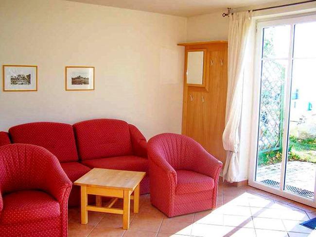 Ferienwohnung mit Ausziehcouch, Sesseln, Tisch und Terrasse
