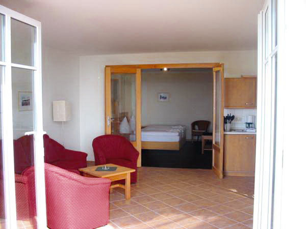 Ferienwohnung mit Wohnraum mit Ausziehcouch, Sesseln, Tisch und Küchenzeile