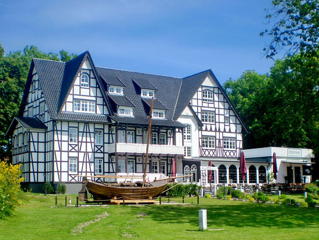 Außenansicht vom Hotel mit Segelboot im Vorgarten, Eingang und Terrasse