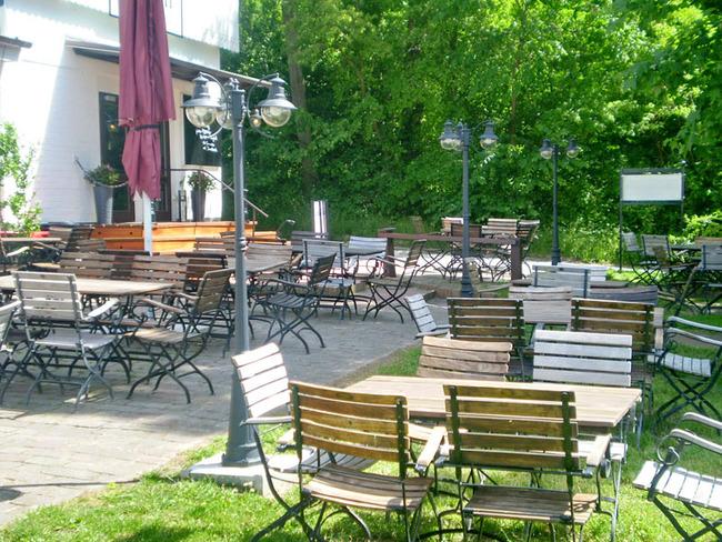 Sonnenterrasse mit vielen Tischen und Stühlen zum gemütlichen Verweilen