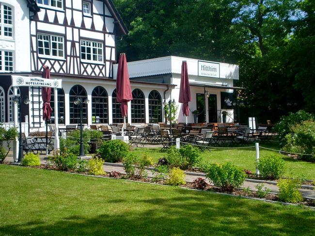 Ausblick auf Hoteleingang und den Garten mit Sonnenterrasse