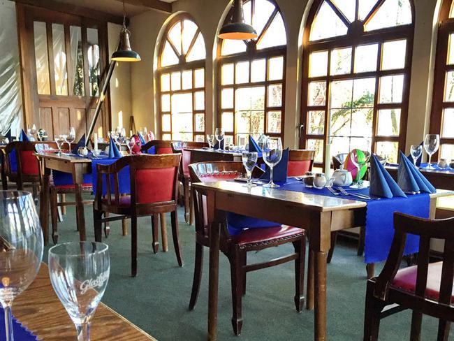 Veranda mit großen Fenstern, gedeckten Tischen und Boddenblick