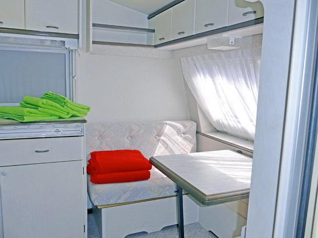 Küche mit umbaubarer Sitzgruppe im kleinen Mietwohnwagen