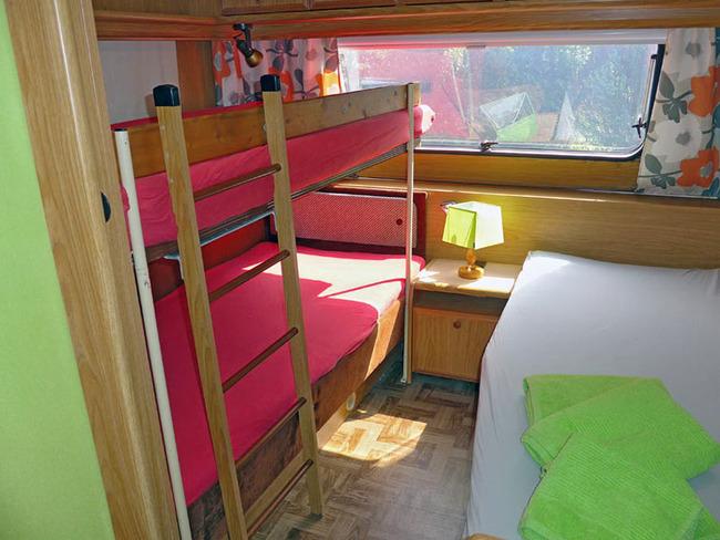 Doppelstockbett und Einzelbett im großen Mietwohnwagen