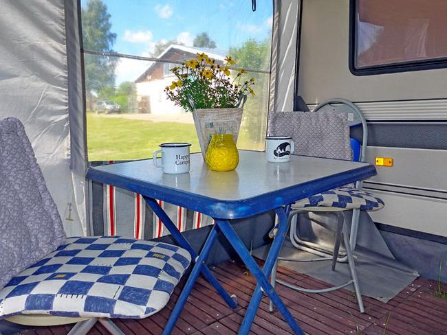 Vorzelt mit einem Tisch und zwei Stühlen am kleinen Mietwohnwagen