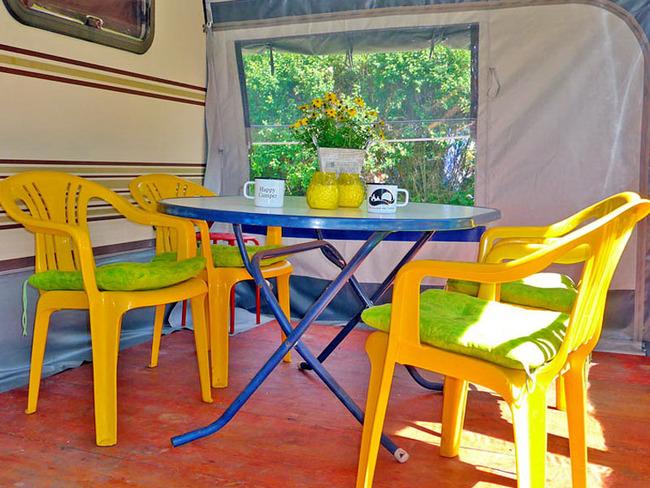 Vorzelt mit einem Tisch und vier Stühlen am großen Mietwohnwagen