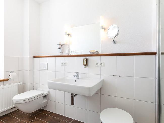 helles Badezimmer mit Fenster, Dusche, Waschbecken, WC und Fön