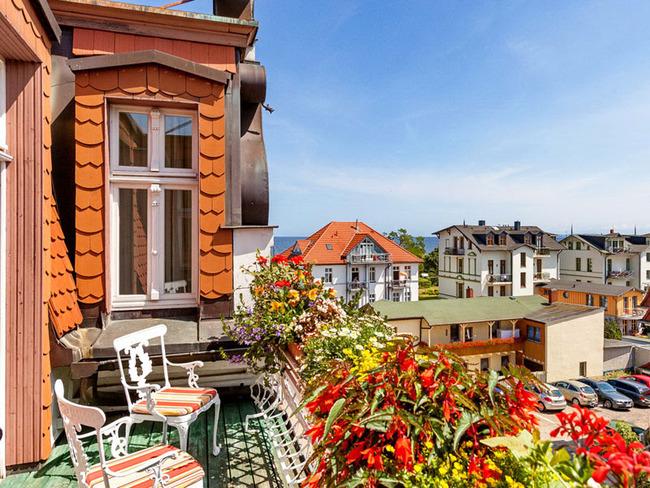 Balkon mit Stühlen, vielen bunten Blumen, Orts- und Meerblick