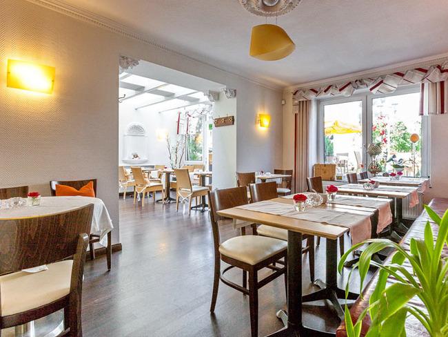 Café mit liebevoll dekoriertem Raum mit Wintergarten und Terrassenblick