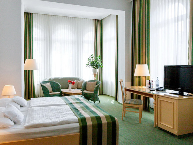 Doppelzimmer mit zwei großen Fensterfronten, Bett, Sitzecke, Schreibtisch, Telefon und TV