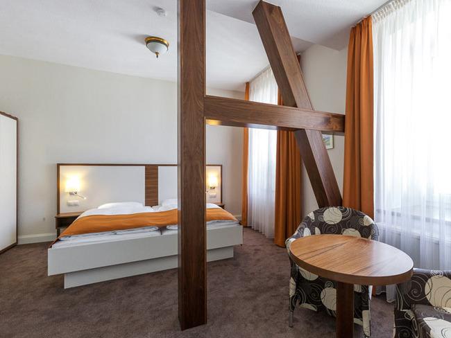 geräumiges Doppelzimmer mit Fachwerk, Bett und Sitzecke
