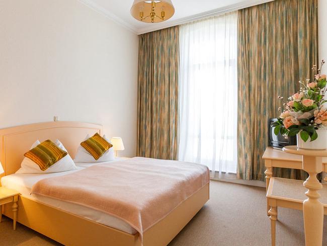 kleines, helles Doppelzimmer mit Bett, TV und Tisch