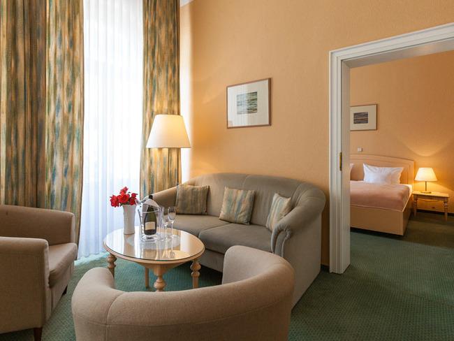 unsere Suite - Wohnraum mit gemütlicher Sitzecke und Schlafzimmer mit Doppelbett