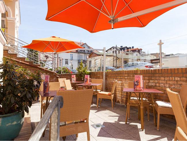 Terrasse am Hoteleingang mit Tischen, Stühlen und Sonnenschirmen
