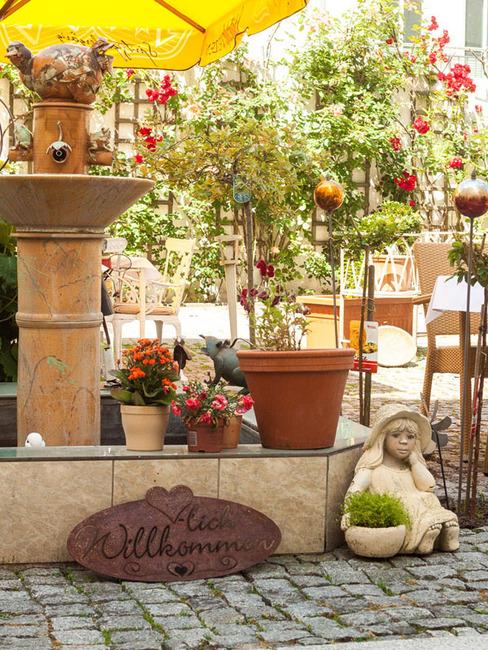 Springbrunnen im Innenhof mit wunderschönen Rosen, Tischen und Stühlen
