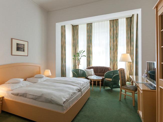 Doppelzimmer mit Bett, Sitzecke mit Sofa und Sesseln, Schreibtisch und TV