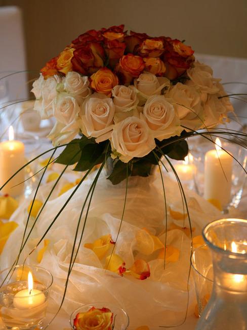 romantisches Arrangement mit roten und apricotfarbenen Rosen und Kerzen