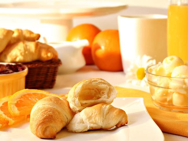 Frühstückstisch mit Croissants, Orangen, Marmelade, Butter und Orangensaft