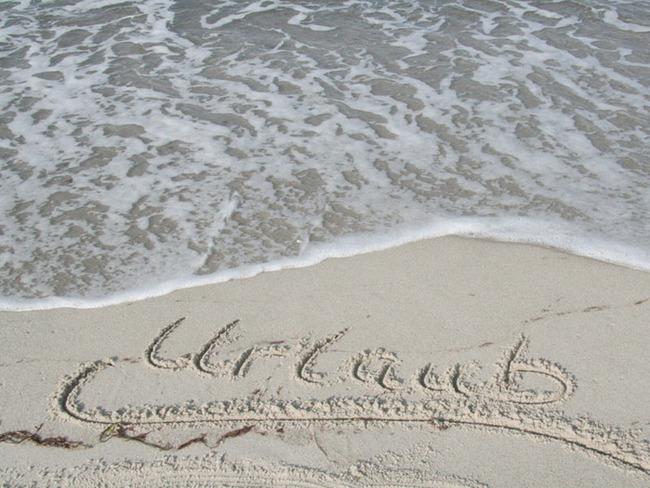 """in den feinen Sand gemalter Spruch """"Urlaub"""" direkt am Ostseeufer"""