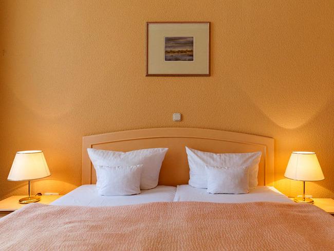 in warmen Farben gestaltetes Schlafzimmer einer Suite mit Doppelbett, Nachttischen und Tischlampen