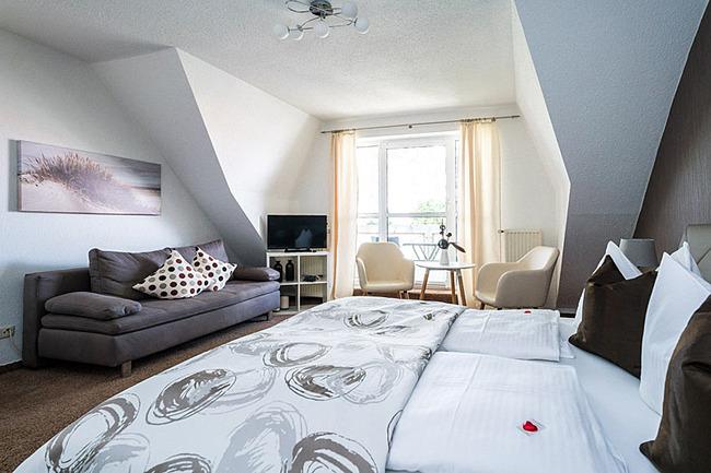 Zimmer mit Doppelbett, Couch, Sessel und TV
