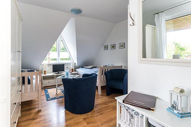 Zimmer mit zwei Sesseln, Couchtisch und zwei Einzelbetten