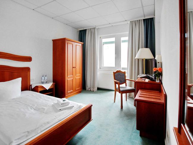 Einzelzimmer mit Doppelbett, Nacht- und Kleiderschrank, Schreibtisch, Stuhl, TV und Telefon