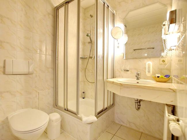 helles Badezimmer mit Dusche, Waschbecken, WC, Spiegel, Fön, Kosmetikspiegel