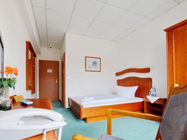 Einzelzimmer mit Doppelbett, Nachttisch, Kleiderschrank, Schreibtisch mit Stuhl, TV, Telefon