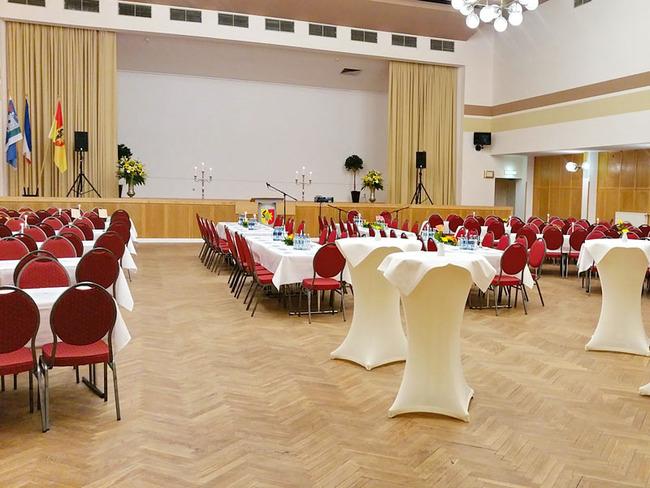 großer Saal mit Bühne und gedeckten Tafeln für eine Feierlichkeit
