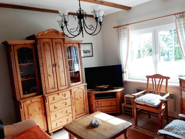 Ferienhaus Wohnraum mit Couch, Vitrine, TV