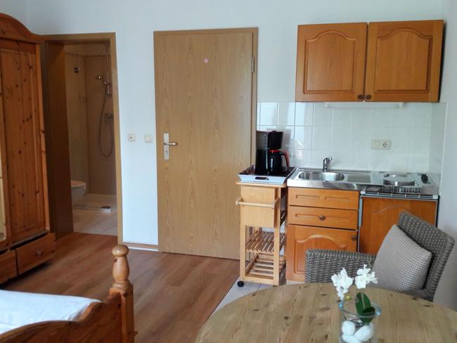 App. 20m² - kleine Küchenzeile im Wohnraum mit Blick ins Badezimmer