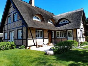 Außenansicht vom reetgedeckten Fachwerkhaus Haus Meerblick mit Sitzbank und Garten