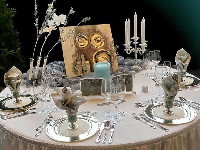 festlich gedeckter runder Tisch mit Kerzen und Blumendeko