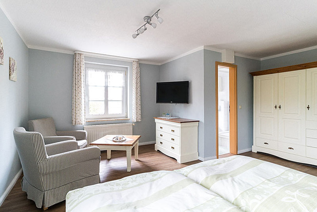 mit hellen Möbeln eingerichtetes Doppelzimmer mit Sitzecke und TV