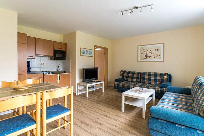 Wohnraum mit Couchecke und offerner Küche mit Esstisch