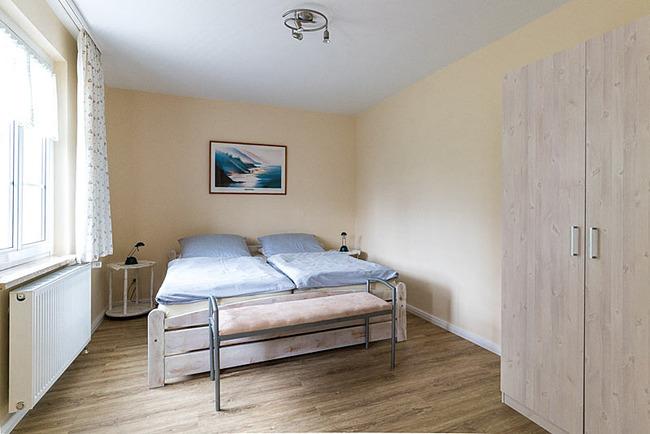 Zimmer mit Doppelbett und Schrank
