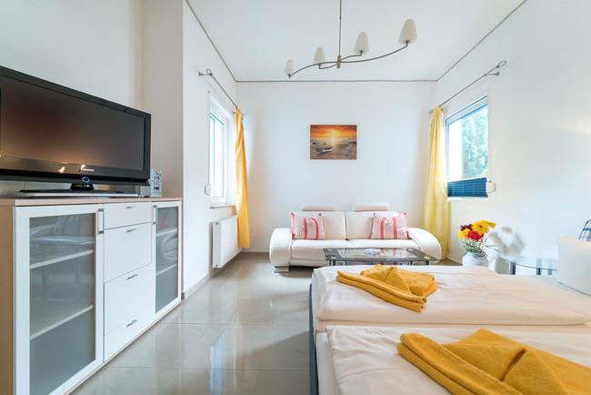 Blick vom Doppelbett auf die Couchecke mit TV