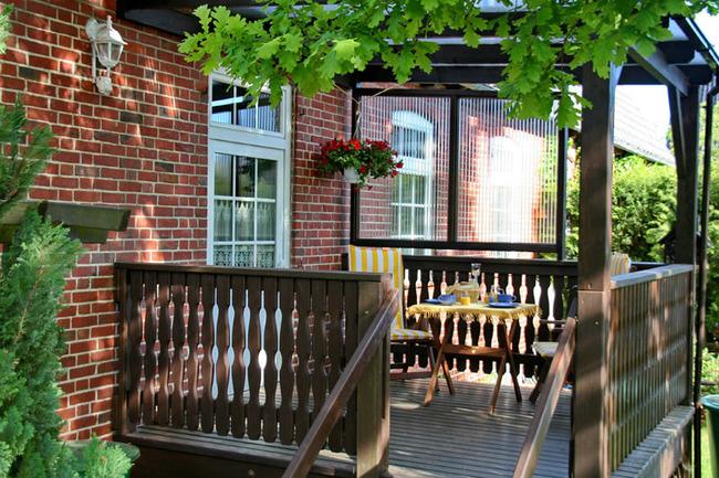 seperater Eingang mit glasüberdachter Terrasse