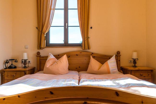 großes Doppelbett mit Fensterblick