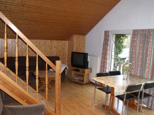 Ferienwohnung - Wohnraum mit Esstisch und Treppe