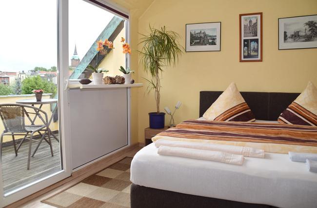 Doppelbettzimmer mit möbliertem Balkon und Blick auf die Schweriner Altstadt