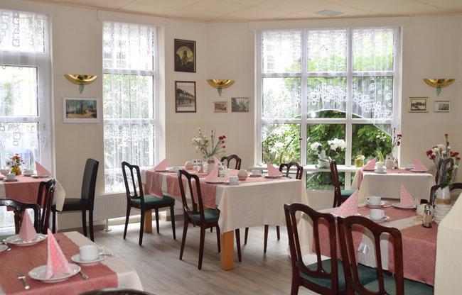 Restaurant mit Frühstückstischen und Blick ins Grüne