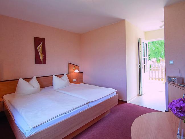 Doppelzimmer mit heller Einrichtung, TV und möblierter Terrasse